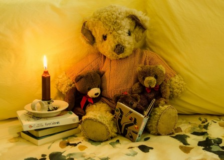 Title: Bedtime story, 4th, Photographer: Bill Anderson, Judge's comments: (A picture that would represent many parents at home at the moment) Well set up and the candle gives a nice ambient lighting and adds to the story