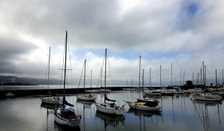 Title: Patchy day, Judge's Comments: The image is of a peaceful scene of boats at anchor, however the dense shadows in the image have lost their detail and the image feels underexposed. I would suggest less sky and more of the reflections.