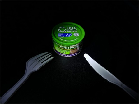 Title: Needs Must!, 3rd, Photography by Paddy Flanagan, Judge's Comments: Oh oh! Did you break your tin opener in lock down? Creative thinking and good composition have created a simple effective image. The knife is brighter than the fork and takes attention away from the tin of tuna, so darken this down slightly. Great idea.