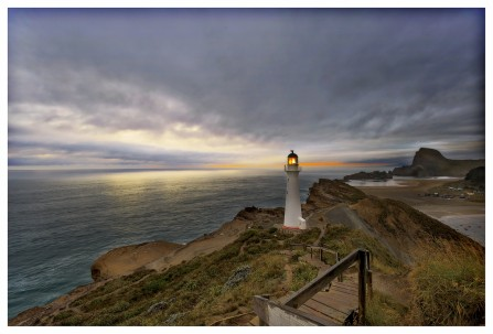Title: The Lighthouse!, 3rd, photography by Kate Hall, Judge's Comments: The light is turned on so well done. I like the wide angle and the position of the lighthouse on the right third for a change with the coastline diagonally dynamic. The light on the water is lovely. Make the most of your leading lines. A couple of steps to the left if possible would have enabled you to use that path more, as the lighter board at the front tends to grab my attention. Perhaps crop just above this