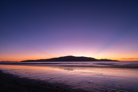 Title: Kapiti Sunset, Judge's Comments: Perfect timing for a beautiful glow in the sky. The nice line of the wet beach also catches the colour. There seems a large amount of sky however and if this was cropped slightly, don't crop the rays of the sun. Just thinking aloud though as I like as it is.
